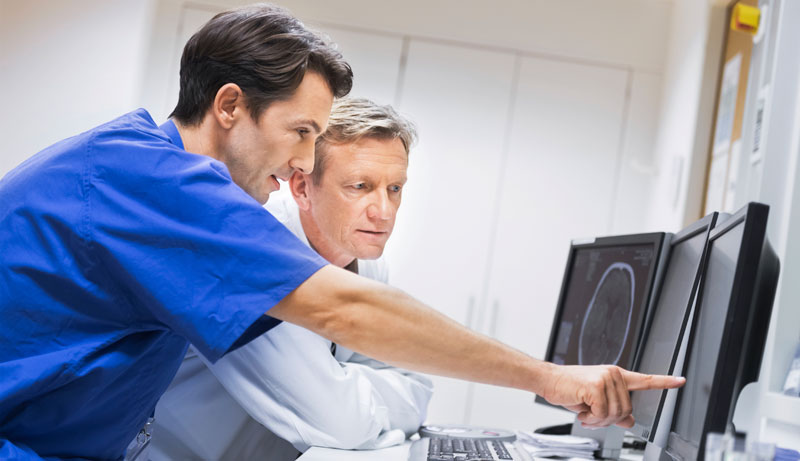 Doctors looking at computer monitor